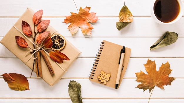 Creative autumn composition with gift, notebook and tea Free Photo
