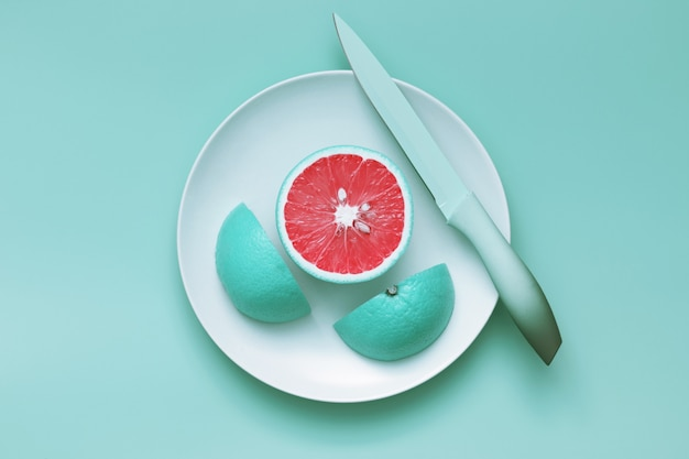 Creative blue grapefruit slices cut on plate with knife Premium Photo