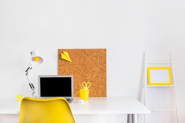 Creative bright cabinet with yellow chair and cork board Free Photo