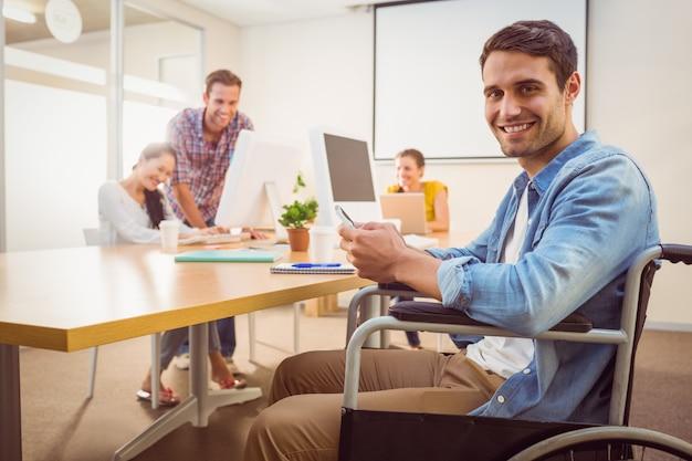 Creative businessman in wheelchair holding a phone Premium Photo