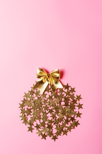 Creative christmas arrangement with golden stars in circle on pink background, conceptual design, copy space Premium Photo
