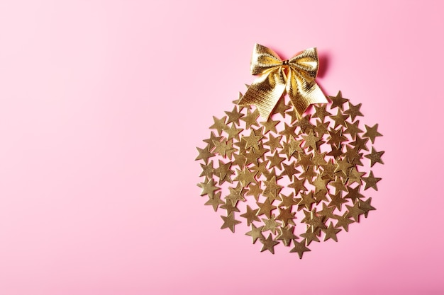 Creative christmas arrangement with golden stars in circle on pink background, glamour concept Premium Photo