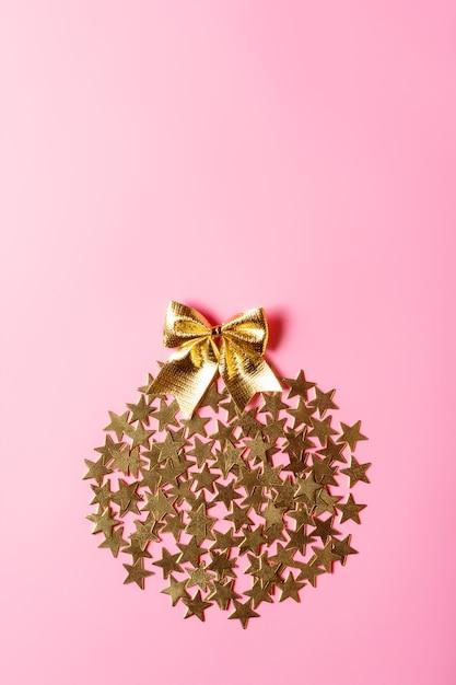 분홍색 배경, 개념 설계, 복사 공간에 동그라미에 황금 별을 가진 창조적 인 크리스마스 배열 프리미엄 사진