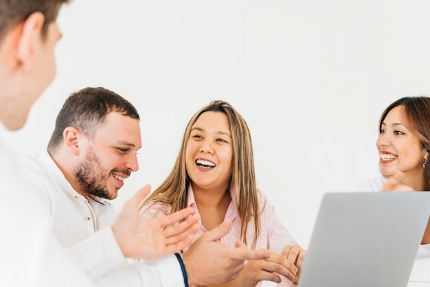 Creative colleagues discussing and laughing in office Free Photo
