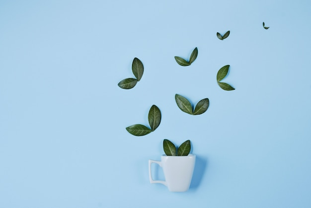 Creative composition. coffee cup with birds made of natural green leaves on blue background Premium Photo