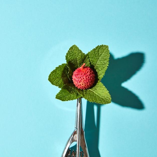 Креативная композиция из фруктов личи с листьями мяты в металлической ложке для мороженого на фоне синего стекла с тенями. еда в современном стиле, вид сверху. Premium Фотографии