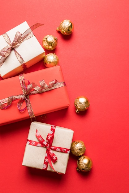 Creative composition with gifts or presents boxes, gold bowson red background. Premium Photo