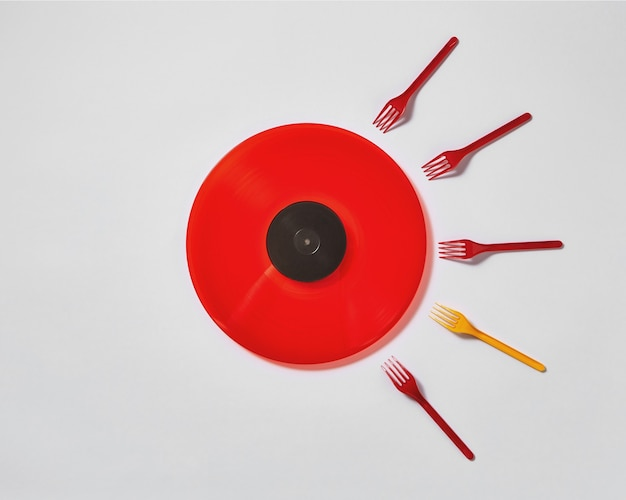 Creative composition with red vinyl record and plastic colored forks Premium Photo