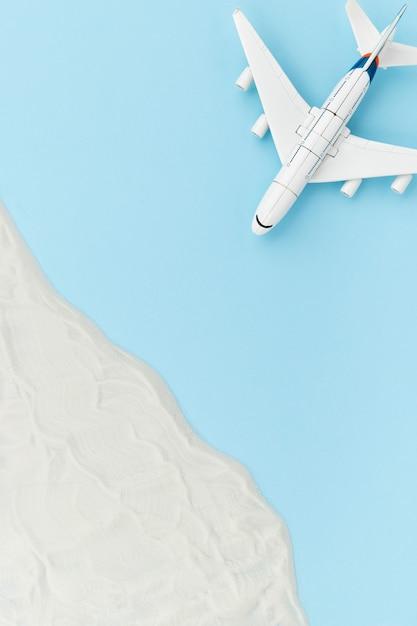 장난감 비행기와 모래 크리 에이 티브 구성입니다. 여행 휴가 개념 프리미엄 사진