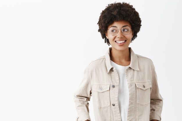 Creative confident and carefree dark-skinned female freelancer in beige shirt and glasses holding hands in pockets gazing left joyfully, spending great time over gray wall Free Photo