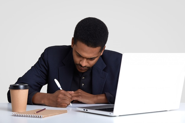 Creative copywriter writes down ideas, sits in front of opened laptop computer, surrounded with notepad, dispoasable cup of hot beverage, poses at work place, isolated on white. Premium Photo