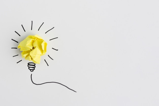 Creative crumpled yellow paper light bulb idea on white background Free Photo
