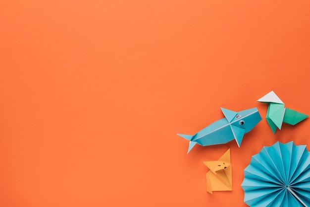 Creativo arte origami decorativi all'angolo di sfondo arancione Foto Gratuite
