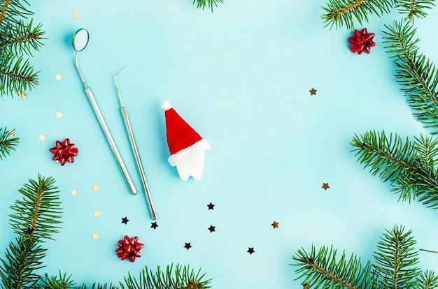 Творческое стоматологическое рождество и новый год. зеркало, зонд и игрушечный зуб в новогодней шапке Premium Фотографии