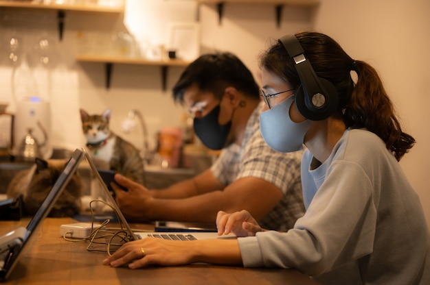 Creative designer business worker, working in spaced and wearing a medical face mask to prevent the spread of the coronavirus covid-2019, home office for  small people group to work from home Premium Photo