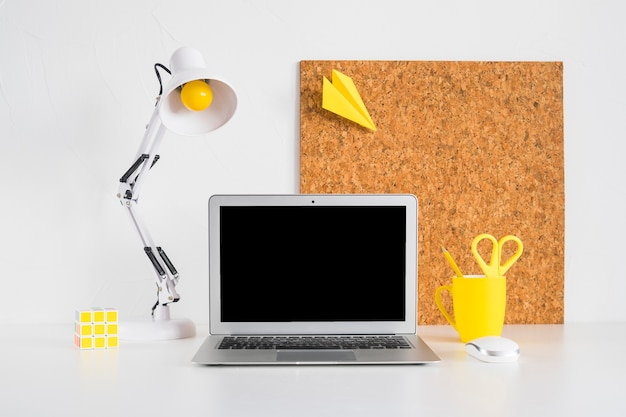 Creative desk with cork board and laptop Free Photo