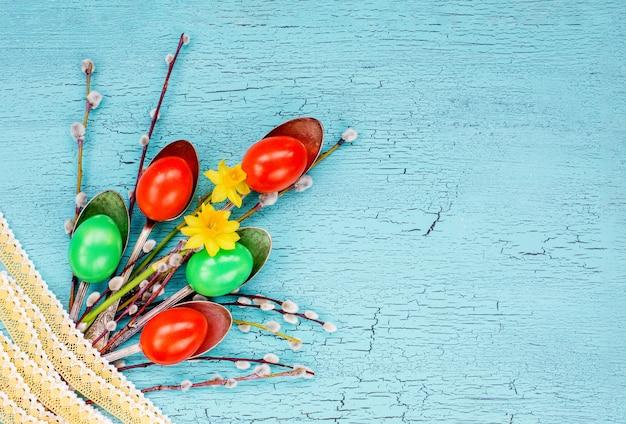 創造的なイースターのブーケ。イースターエッグ、スプーン、柳の枝、レース、花。トップビュー、コピースペース、イースターの背景 Premium写真