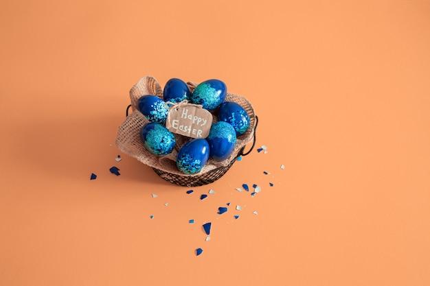 カラフルな卵と青の背景に花で作られた創造的なイースターレイアウト。サークルリースフラットレイアウトコンセプト。イースター休暇のコンセプトです。 無料写真