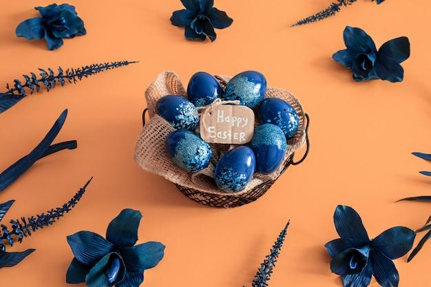 カラフルな卵と青の花で作られた創造的なイースターレイアウト。 無料写真