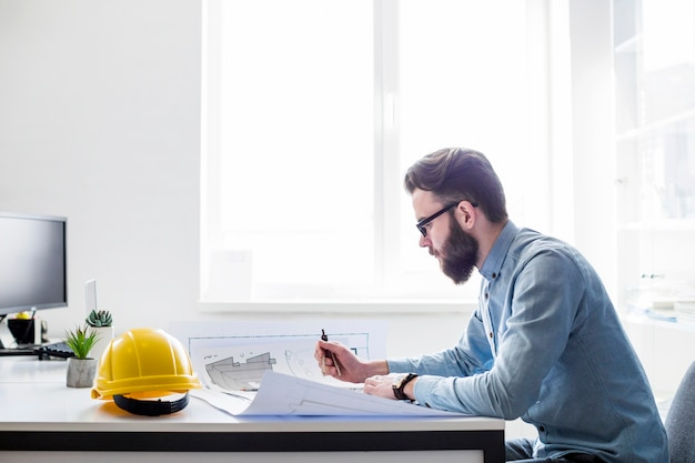 Творческий инженер, работающий над проектом строительства на рабочем месте Premium Фотографии