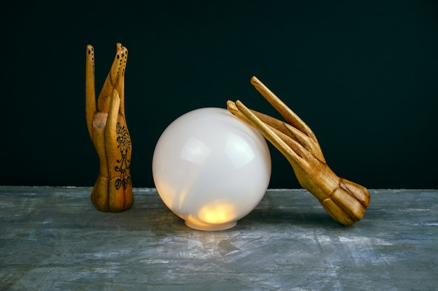 Creative esoteric still life with a ball of predictions and two wooden female hands Premium Photo