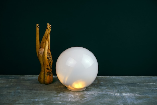 Creative esoteric still life with a ball of predictions and wooden female hand Premium Photo