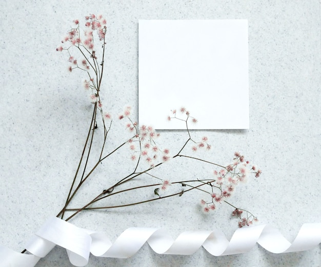 Creative flat lay design of card note with flower. Premium Photo
