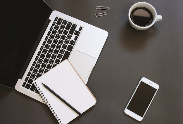 Creative flat lay design of workspace desk with laptop, notebook, smartphone and coffee with copy space background Free Photo
