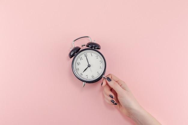 黒のヴィンテージ目覚まし時計を持っている女性の手の創造的なフラットレイ朝の時間の感情の概念上面図 Premium写真