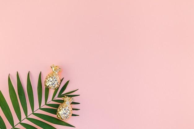 緑の熱帯のヤシの葉の創造的なフラットレイトップビューは、パイナップルのコピースペースとミレニアルピンクの紙の背景を残します Premium写真