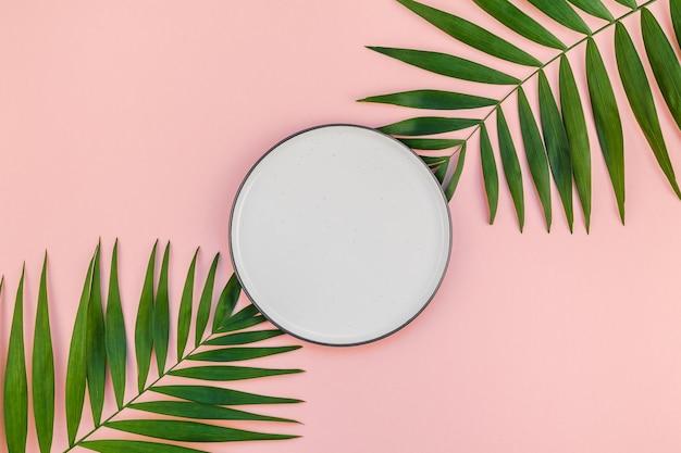 空のプレートと緑の熱帯ヤシの葉の創造的なフラットレイ上面図 Premium写真