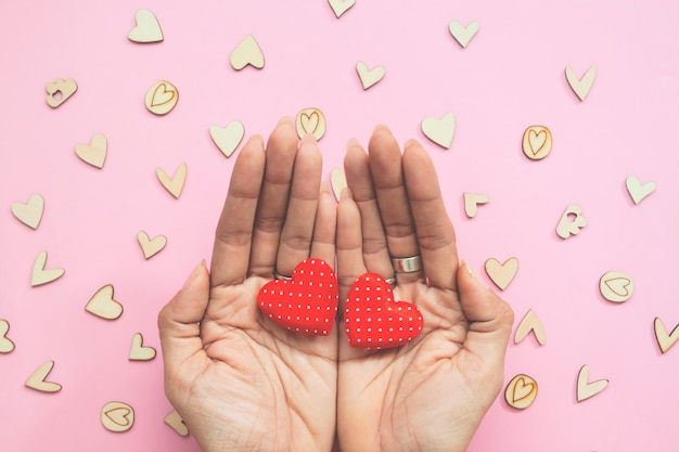 Creative flat lay of woman's hands with two hearts on pastel background. Premium Photo