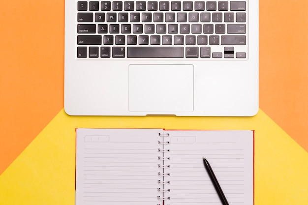 Creative flat lay of workplace desk with orange and yellow background Free Photo