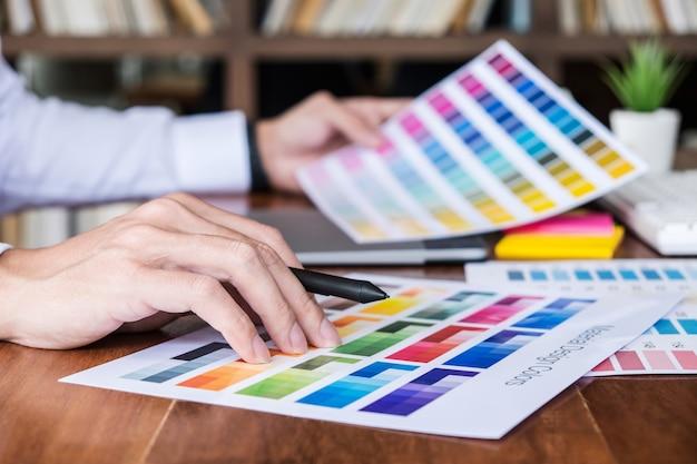 Креативный графический дизайнер, работающий над выбором цвета и нанесением на графический планшет Premium Фотографии