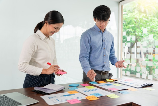Creative group of business people brainstorming use sticky notes picking to share idea Premium Photo