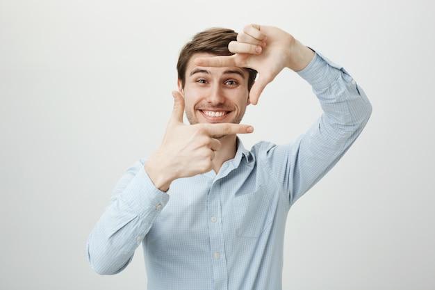 創造的なハンサムな男笑顔、ハンドフレームを表示、瞬間をキャプチャ 無料写真