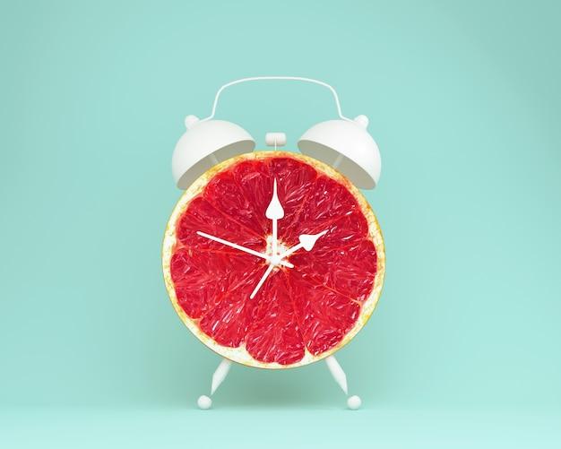 Creative idea layout fresh grapefruit slice alarm clock on blue background. minimal fruit Premium Photo