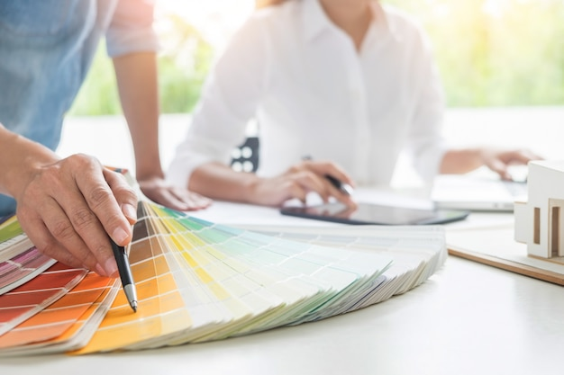 Creative or interior designers teamwork with pantone swatch and building plans on office desk, architects choosing color samples for design project Premium Photo