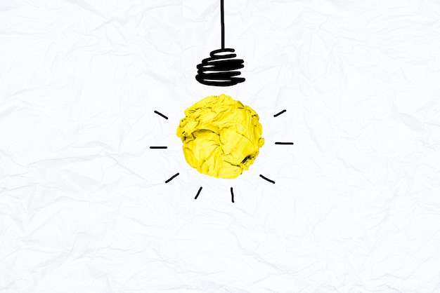 Creative iyellow crumpled paper light bulb on white recycle papaer background. Premium Photo