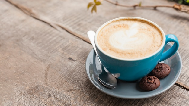 Creative latte art coffee cup with two baked cookies on wooden desk Free Photo