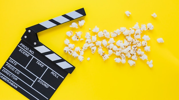 Creative layout of clapperboard and popcorn Premium Photo