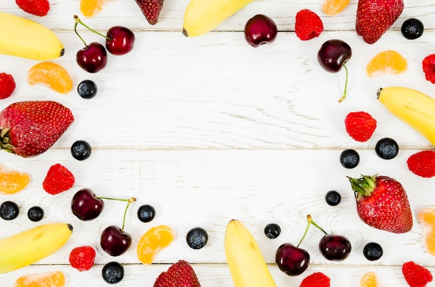 Creative layout of fruits on wooden background Free Photo