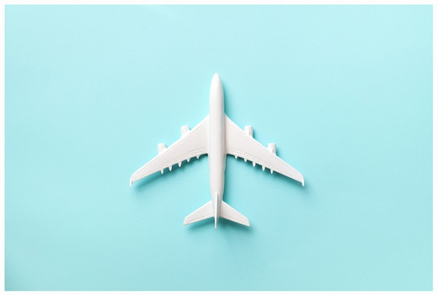 Creative layout. top view of white model plane, airplane toy on pink pastel background. Premium Photo