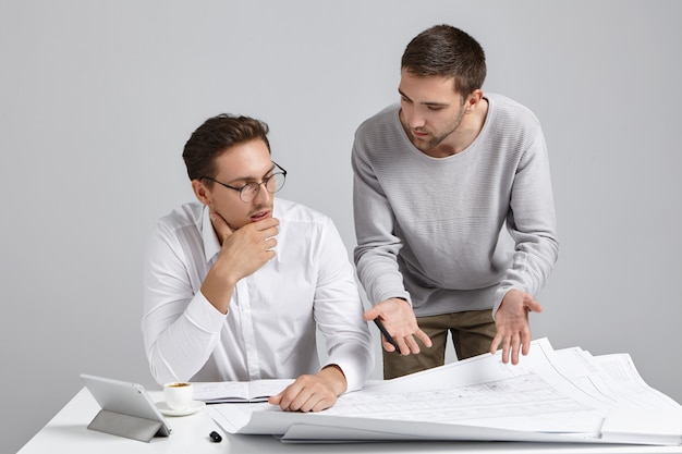 Creative male designer wears casual sweater, presents his ideas and designing project to employer, Free Photo