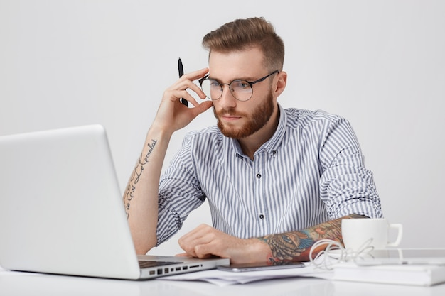 Creative male editor with tattooes, looks confidently into screen of laptop, works hard, surrounded with modern smart phone Free Photo