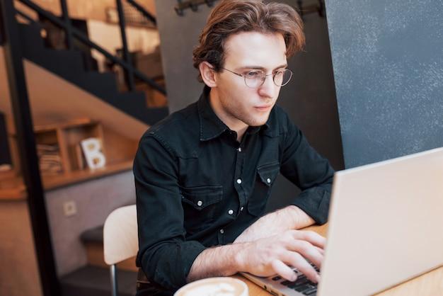 Творческий человек дизайнер работает на своем ноутбуке во время утреннего завтрака в современном интерьере кафе Бесплатные Фотографии