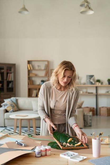 緑の葉や植物から構成を作り、それを木枠に入れるインテリアの創造的な成熟した女性デザイナー Premium写真