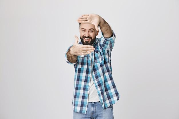 創造的な中年男が瞬間を捉え、手フレームのジェスチャーを表示 無料写真