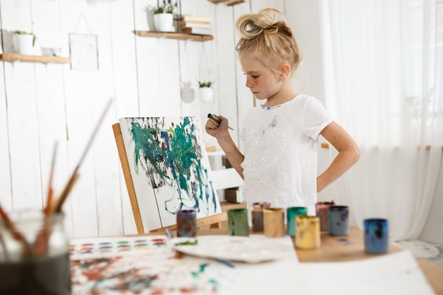 Creative, occupied female child standing behind easel, working on her new picture. l Free Photo