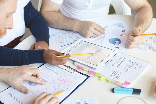 Творческие люди разных национальностей вместе работают над бизнес-планом, анализируют темпы роста, стоимость товаров и услуг, изучают рынок, подсчитывают убытки, используют компьютер с сенсорной панелью и делают заметки. Бесплатные Фотографии
